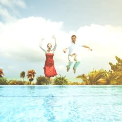 Couple jump hand in hand into swimming pool