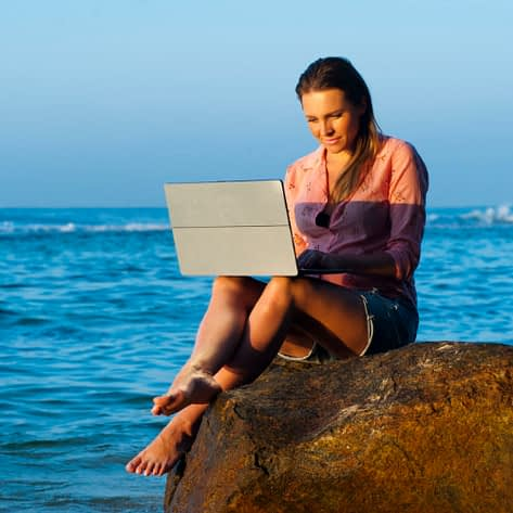 Woman telecommutes from Dominican Republic while working on the beach with computer